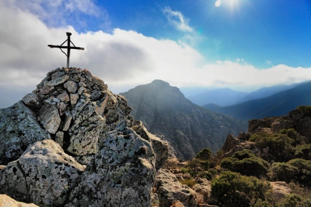 The small cross and cairn at the top of Capu di a Veta behind the citadel town of Calvi in the Balagne region of Corsica photo