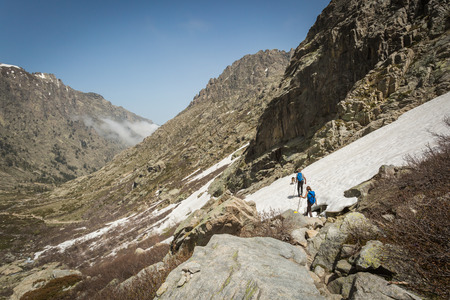 lac: Two hikers and two dogs traversing the snow in the mountains of Restonica near Lac de Melo Stock Photo