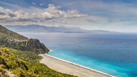 The black beach and village of Nonza on Cap Corse in Corsica with Desert des Agriates in the background photo