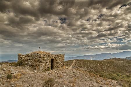 Dark clouds over an old bergerie in the hills near Col de San Colombanu in the Balagne region of Corsica photo
