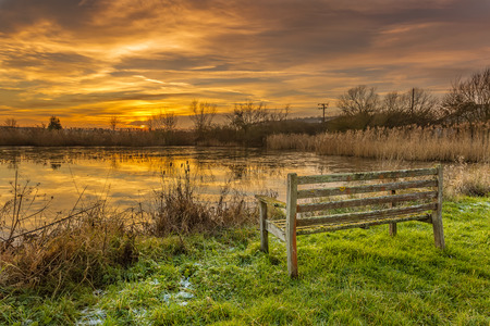 An old park bench looking across a frozen pond towards the setting sun photo