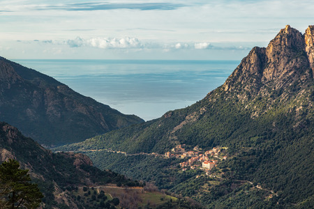 The village of Ota in Corsica with mountains and the Mediterranean sea behind Stock Photo