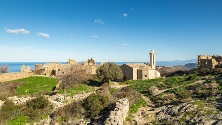 restored: Ruined buildings and the restored church in the abandoned village of Occi near Lumio in the Balagne region of Corsica