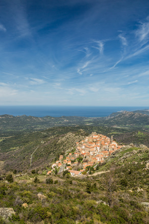 the crags: The mountain village of Speloncato in the Balagne region of north Corsica with maquis and the Mediterranean in the background against a blue sky and wispy clouds