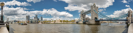 Panorama of Tower Bridge the Tower of London and the city with the river Thames in foreground with blue skies and fluffy clouds