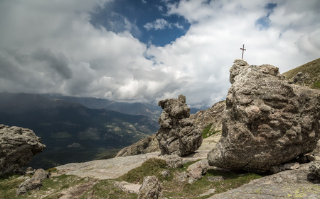 lac: Iron cross in the rock near Lac De Nino in Corsica and  dark clouds and mountains in the background Stock Photo