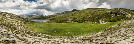 lac: Panoramic view across Lac De Nino in Corsica with a stream meandering across a green plain in foreground and  dark clouds and snow capped mountains in the background Stock Photo