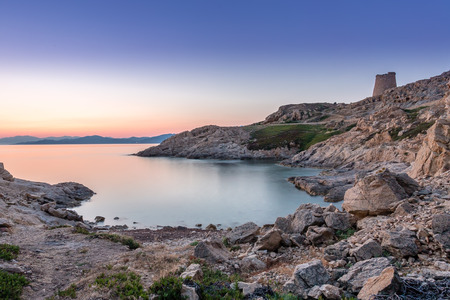 genoese: Sunrise in the bay at Ile Rousse in Corsica with a calm mediterranean sea and a Genoese tower in the foreground and mountains of the desert des agriates in the background Stock Photo