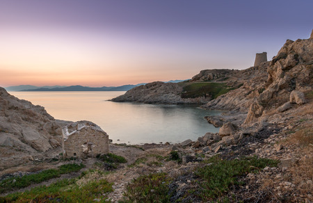 genoese: Sunrise in the bay at Ile Rousse in Corsica with an abandoned building in the foreground and a Genoese tower and mountains of desert des agriates in the background Stock Photo