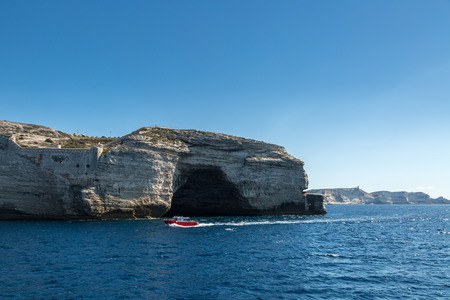 dark cave: Red tour boat passing a dark cave in the white cliffs near Bonifacio harbour in south Corsica with clear blue skies