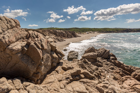 turquise: Rocks, beach and coastline of Sardinia near Rena Majore on the west coast with blue skies and fluffy clouds Stock Photo