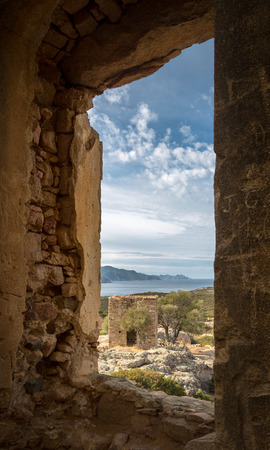 bonaparte: View of derelict building and coastline of Corsica taken through a stone window frame at the ruined chateau of Pierre-Napoleon Bonaparte between Calvi and Galeria