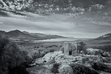 bonaparte: Black  white view of derelict building built on rock outcrop and coastline of Corsica taken from the ruined chateau of Pierre-Napoleon Bonaparte between Calvi and Galeria Stock Photo
