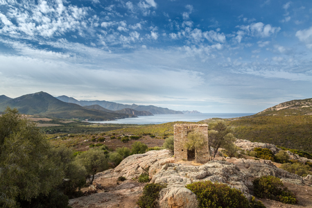 bonaparte: View of derelict building built on rock outcrop and coastline of Corsica taken from the ruined chateau of Pierre-Napoleon Bonaparte between Calvi and Galeria