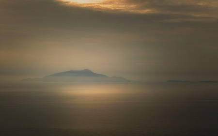 surrounds: Mist surrounds the Italian islands of Isola dIschia and Procida on the west coast of Italy with dark and moody skies above Stock Photo