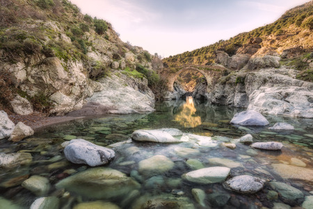 flowing river: Translucent flowing river passing below ancient arched Genoese bridge at Asco in Corsica with rocks, pebbles  boulders in the foreground