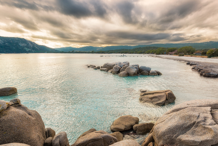 Rocks and boulders in a translucent turquoise sea with a jetty in the background and cloudy skies at Santa Giulia beach in Corsica