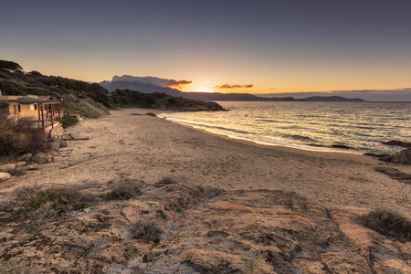 plage: Plage de Petra Muna near Calvi at sunset with rocks in the foreground, beach, mediterranean sea and Calvi in the distance Stock Photo