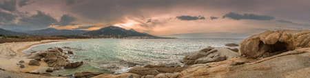 beach panorama: Panoramic view of dramatic moody sky over Algajola beach in Corsica with rocks and sand in the foreground and the village in the background