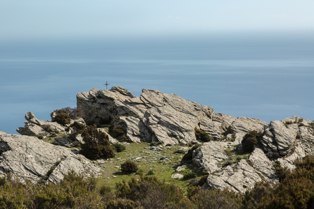 iron cross: Rough iron cross in the rock looking out over the east coast of Corsica Stock Photo