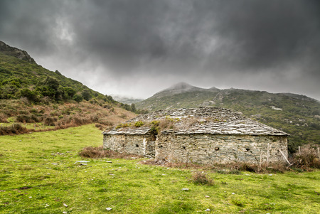 moody: Glaciere ice storage building in the hills above Bastia in northern Corsica with moody grey sky