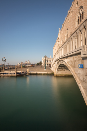 ducale: A gondola passes under a bridge by the Doges palace or Palazzo Ducale in Venice