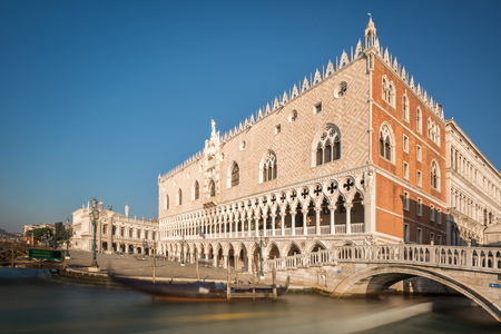 A slow shutter image of boats passing under a bridge by the Doges palace or Palazzo Ducale near Piazza San Marco in Venice