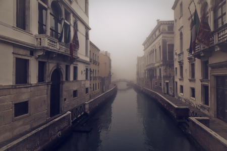 envelops: Early morning mist envelops buildings and a bridge on a canal in Venice