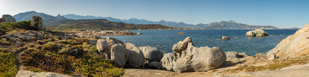 towards: Panoramic view from Punta Spano at Sant Ambroggio in Corsica across Calvi bay towards Calvi with shallow, turquoise water and rocks in the foreground and blue sky above