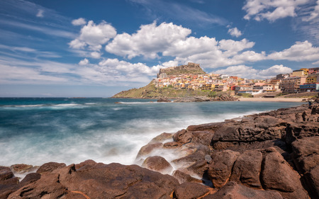 Slow shutter image of waves crashing onto rocks at Castelsardo on the coast of Sardinia in Italy with rocks in the foreground and blue skies and fluffy clouds Stock fotó