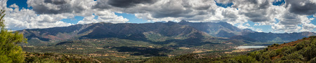 lush: Panoramic view of the lush green Regino valley in the Balagne region of Corsica with mountains and mountain villages behind beneath a blue sky with fluffy white clouds and maquis in the foreground