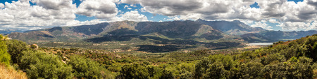 Panoramic view of the lush green Regino valley in the Balagne region of Corsica with mountains and mountain villages behind beneath a blue sky with fluffy white clouds and maquis in the foreground
