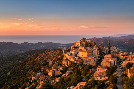 The Balagne village of Speloncato in Corsica bathed in late evening sunshine with the Regino valley and Mediterranean sea behind and pink, orange and deep blue skies above Stock Photo