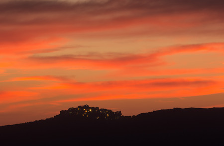glisten: Lights glisten in the hilltop village of Sant Antonino in Balagne region of Corsica silhouetted against a dramatic pink evening sky Stock Photo