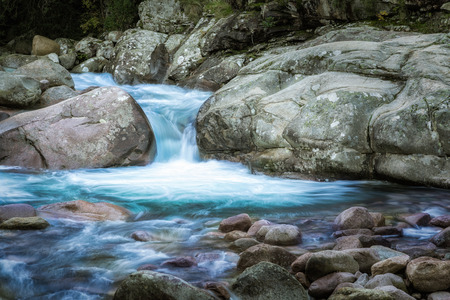 Slow shutter image of the cascading Figarella river flowing between two boulders in the Bonifatu forest near Calvi in Corsica with rocks in the foreground