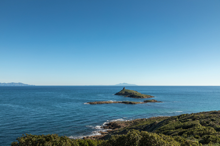 Genoese tower on Les Iles Finocchiarola off the coast of Cap Corse in Corsica with the  islands of Capraia and Elba in the distance on a clear blue sunny day