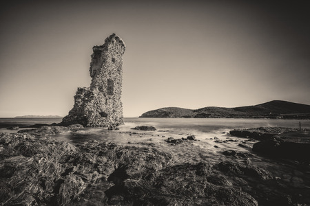 genoese: Black & White image of Genoese tower of Santa Maria della Chiappella at Rogliano on the east coast of Cap Corse in Corsica with rocks in the foreground