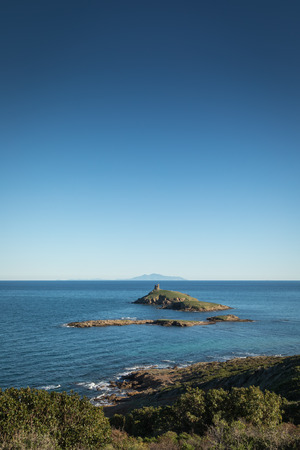 Genoese tower on Les Iles Finocchiarola off the coast of Cap Corse in Corsica with the  island of Elba in the distance on a clear blue sunny day