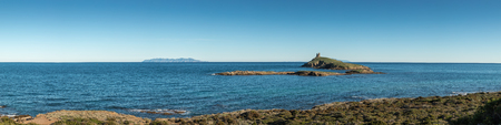 corse: Panoramic view of the Genoese tower on Les Iles Finocchiarola off the coast of Cap Corse in Corsica with the  islands of Elba and Capraia in the distance on a clear blue sunny day