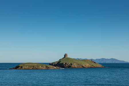genoese: Genoese tower on Les Iles Finocchiarola off the coast of Cap Corse in Corsica with the coastline and mountains of the island of Capraia in the distance on a clear blue sunny day