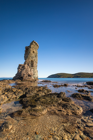 corse: Genoese tower of Santa Maria della Chiappella at Rogliano on the east coast of Cap Corse in Corsica with rocks in the foreground on a clear blue sunny day Stock Photo