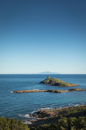 genoese: Genoese tower on Les Iles Finocchiarola off the coast of Cap Corse in Corsica with the  island of Elba in the distance on a clear blue sunny day
