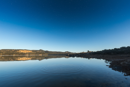 Ripples on a mirror calm lac de Codole in the Balagne region of Corsica at dawn with stars still visible against a clear blue sky