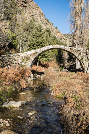 An ancient stone Genoese bridge crossing a stream in the mountains of the Tartagine valley near Mausoleo in the Balagne region of Corsica Stock Photo
