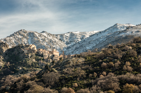 The ancient hilltop village of Speloncato in the Balagne region of Corsica with snow capped mountains behind