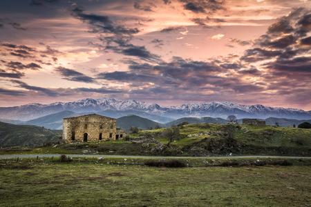 amanecer: Dramatic purple and pink dawn breaking over an old farm building in the Balagne region of Corsica with a small tarmac road passing by and snow capped mountains in the distance