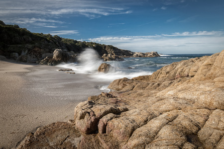 Waves crashing onto rocks and a golden sandy beach at a small cove near Lumio in the Balagne region of Corsica bordered by rocks with  blue skies with wispy clouds above