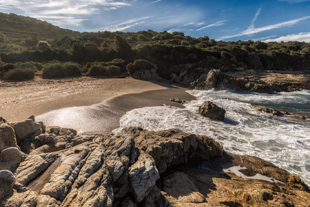 Waves washing onto rocks and a golden sandy beach at a small cove near Lumio in the Balagne region of Corsica bordered by rocks with  blue skies with wispy clouds above