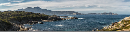 Panoramic view across Calvi bay in the Balagne region of Corsica towards the citadel of Calvi and the lighthouse of Revellata with a rocky headland and ruins of Genoese tower at Punta Caldanu in the foreground