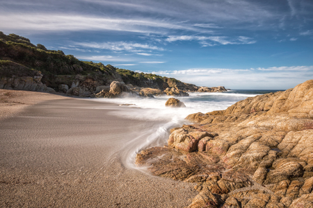 Slow shutter image of waves washing onto a golden sandy beach at a small cove near Lumio in the Balagne region of Corsica bordered by rocks with  blue skies with wispy clouds above Stock Photo